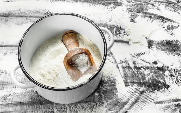 鍋にシャベルを入れて小麦粉をまぶします。石のテーブルの上。