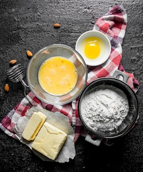 Flour with butter and egg on napkin on black rustic table