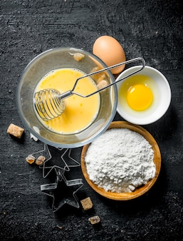 Flour with eggs and forms for the preparation of cookies. on black rustic surface