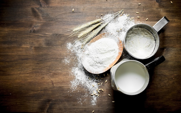 Flour with milk in a jug and spikelets. on wooden table