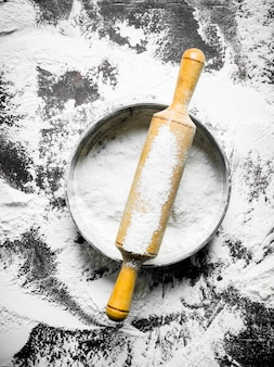 Flour with rolling pin and sieve on rustic table.