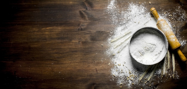 Flour with a sieve, rolling pin and spikelets on wooden table