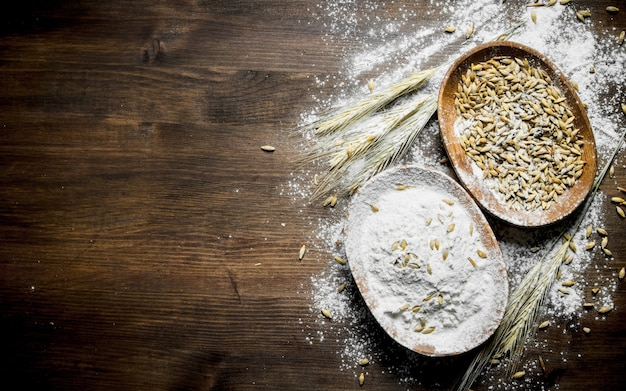 Flour with spikelets and grain in bowl. on wooden table