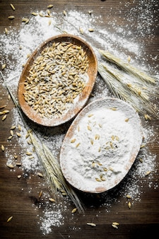 Flour with spikelets and grain in bowl. on wooden