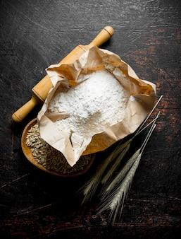 Flour with wheat grain and spikelets. on dark rustic table