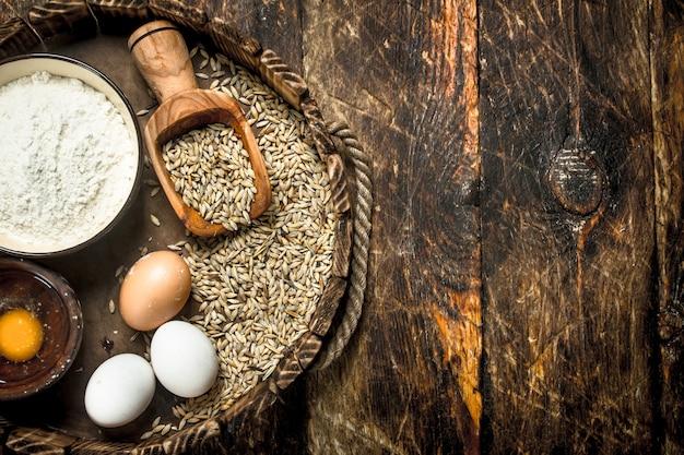 古いトレイに小麦粉をまぶします。木製の背景に。