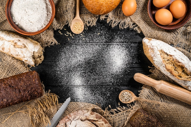 Flour in a wooden bowl on dark wooden table with spikelets of wheat, eggs, milk and butter, top view with copy space.