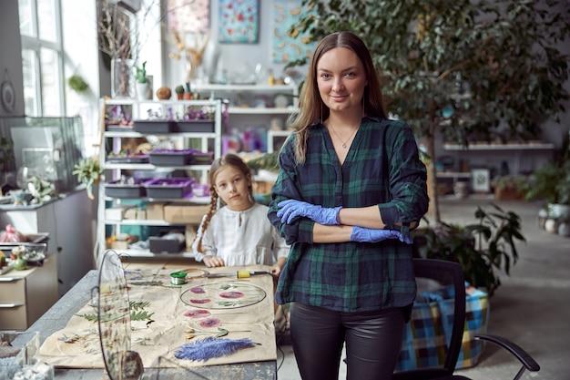다양한 종류의 말린 꽃이있는 밀가루 가게. 젊은 행복 자신감 전문가는 그녀의 여자 아이와 함께 노력하고 있습니다.