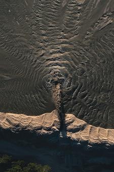 모래 파를 추출하는 동안 모래와 함께 더러운 물의 흐름이 채석장 표면에 분산됩니다 ... 프리미엄 사진