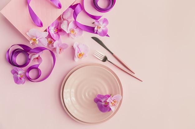 Верхняя композиция из цветов и сервировки стола на светло-розовой поверхности