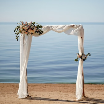 Flower arch on the lake shore. background for wedding invitations.