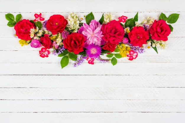 Цветочная композиция бордюр разных полевых и садовых цветов из роз, пионов и жасмина на белой древесине