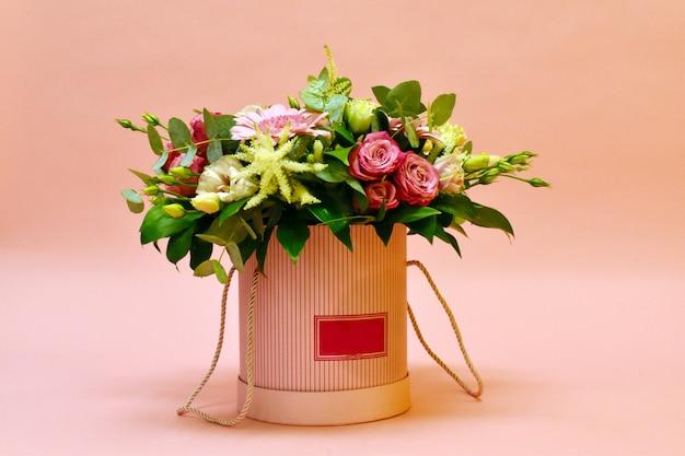 ピンクの背景のフラワーアレンジメント。ボックスに美しい花。