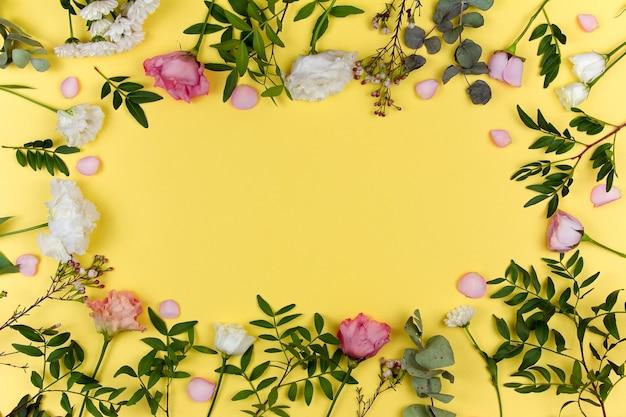 フラワーアレンジメント。黄色の背景にピンクと白の花。バレンタイン・デー。フラットレイ、上面図、コピースペース。