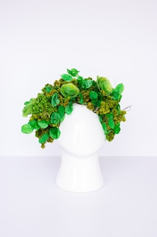 頭の形をしたポットと乾燥した緑の花のフラワーアレンジメント