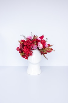 頭の形をしたポットと乾燥した赤い花のフラワーアレンジメント