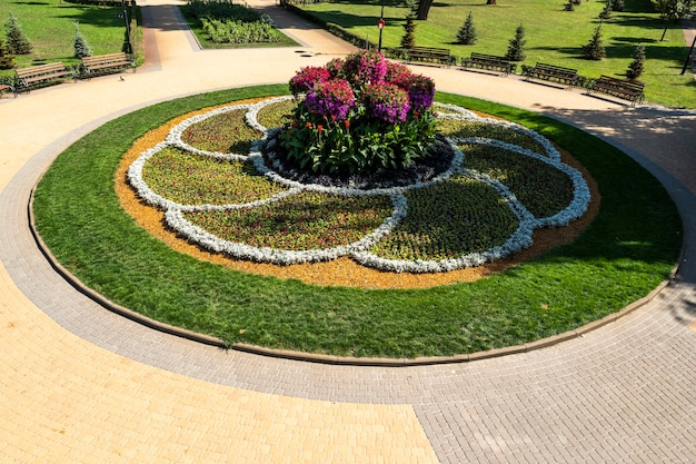 Flower bed with patterns of flowers in the landscape of a city leisure park with seating along a tile path and using oak powder