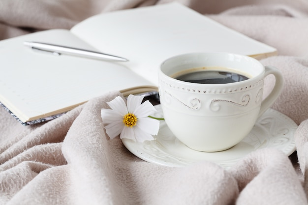 Flower on the book and the cup of black coffee in front of the window in the morning