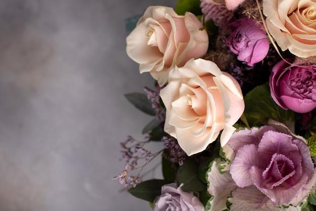 灰色の背景に各種の新鮮な花の花のボーダー。水平方向の画像、コピースペース、トップビュー