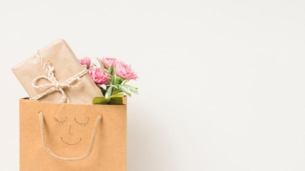 Букет цветов и упакованная подарочная коробка в бумажном пакете с рисованной лицом на белом фоне