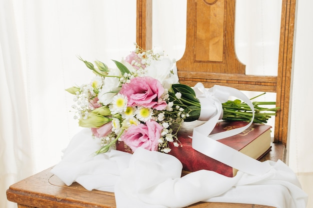 Flower bouquet on book with scarf on wooden chair