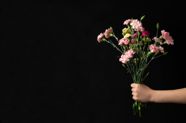 Flower bouquet in boy hand with black copyspace. mothers day concept