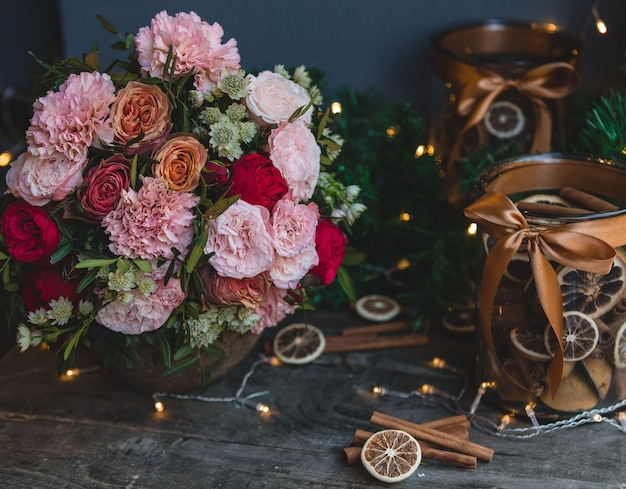 Flower bouquet, christmas ligths and cinnamon decoration sticks.