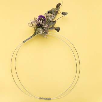 Flower bouquet on empty metallic ring over the yellow backdrop