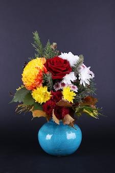 濃い灰色のスペースに青い花瓶の花の花束