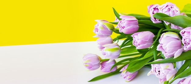 The flower bouquet lies on a white table. purple, unusual lilac tulips with green leaves. bright wide banner and place for text