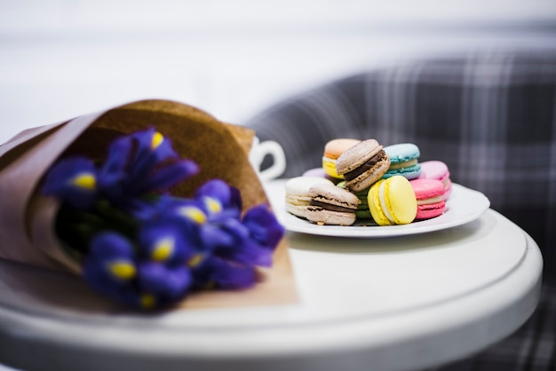 Flower bouquet and macaroons plate on white table