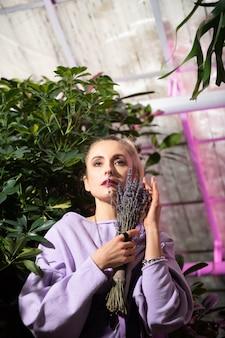 花束。美しい花を手に立って、思慮深い表情を持つ素敵なきれいな女性