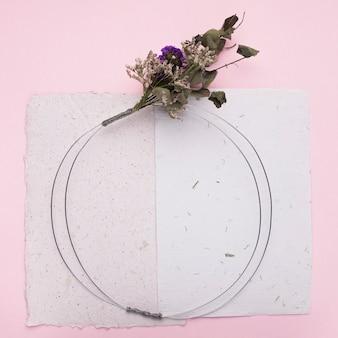 ピンクの背景の紙の上の丸いリングに花の花束