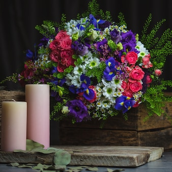 Flower bouquet and pink candles on a rustic wooden space.
