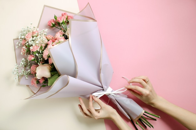 Flower bouquet in pink and nude background. top view on woman decorates a bouquet
