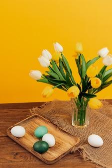 フラワーブーケショップカラフルな卵木製トレイ黄色の壁。