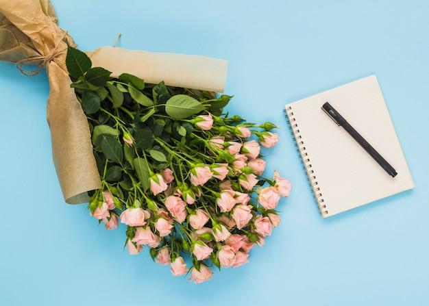 花束;スパイラルメモ帳とペン、青い背景