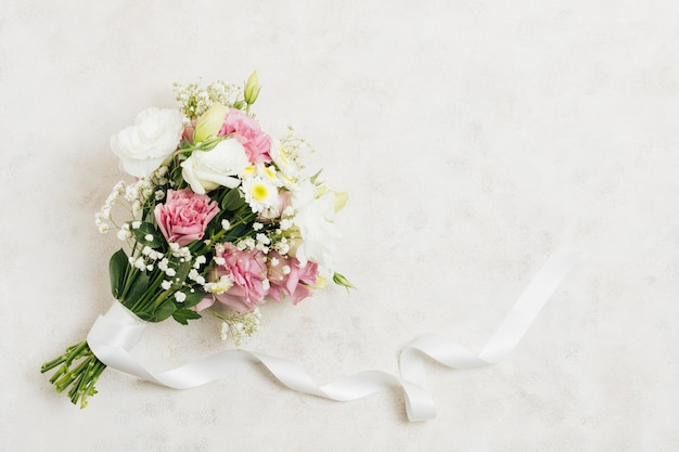 Flower bouquet tied with white ribbon on white backdrop