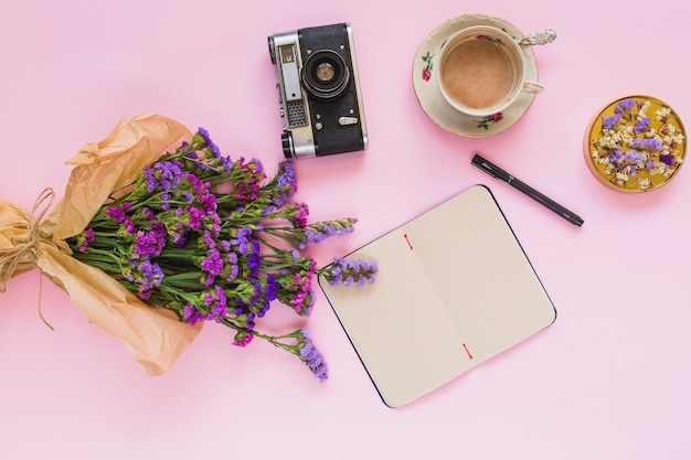 Flower bouquet; vintage camera; diary; pen; coffee cup and coaster on pink background