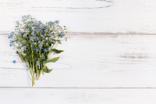 Flower bouquet on a white rustic wooden background