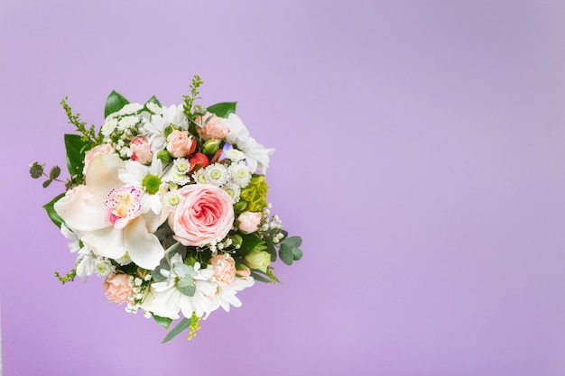 Flower bouquet with gift boxes on purple background with copy space. flat lay, top view floral valentine's day or mother's day concept