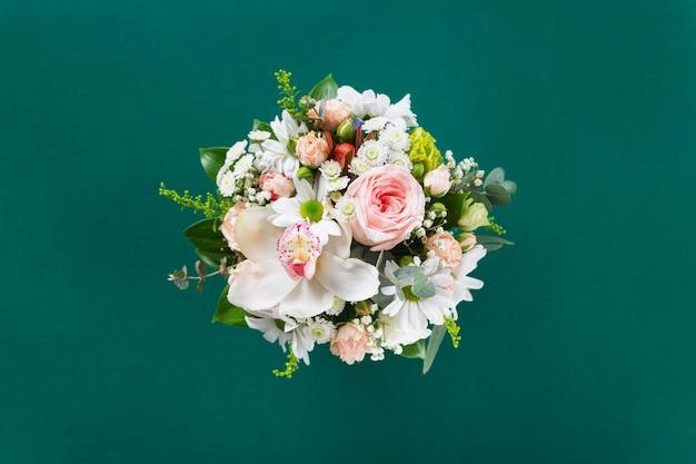 Букет цветов с подарком на зеленом фоне плоские лежал, вид сверху. день святого валентина, концепция любви