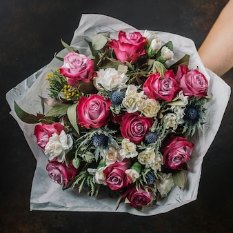 Flower bouquet with pink roses, blue thistle, mimosa and white roses