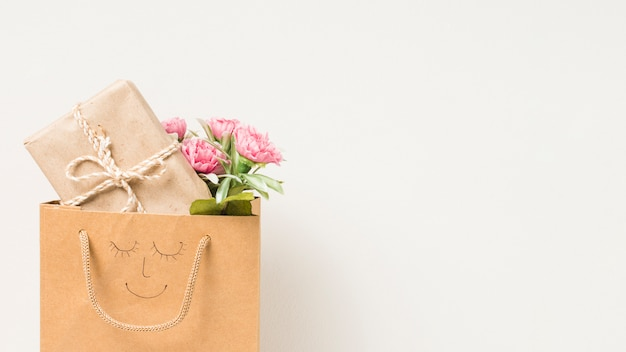 Flower bouquet and wrapped gift box in paper bag with hand drawn face isolated on white background