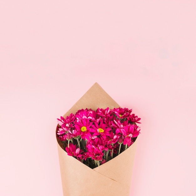 Flower bouquet wrapped with brown paper against pink background