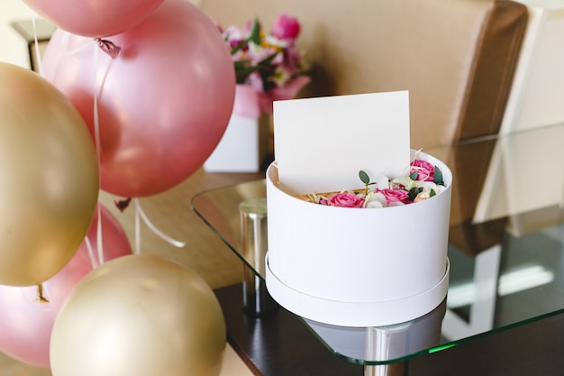 Flower box with blank card,roses flower composition. gift bouquet for mothers day, womens day, birthday and greeting card, gift card inside with empty space for your design, logo. festive balloons