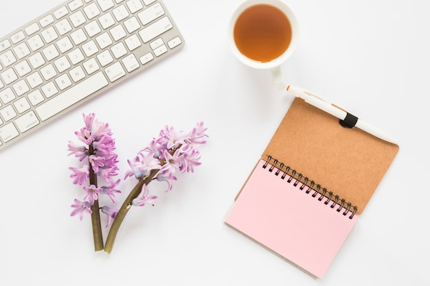 Flower branches with notebook, keyboard and tea cup