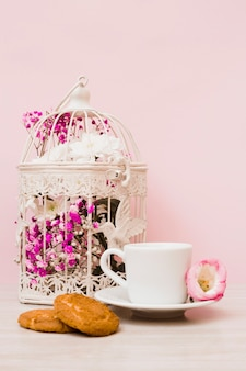 Flower cage; coffee cup and cookies on wooden desk against pastel pink background