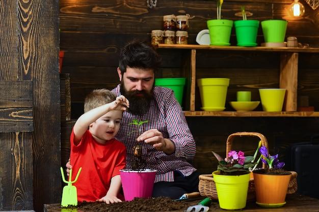 꽃 관리 급수. 토양 비료. 부자. 봄 꽃과 함께 행복 한 정원사입니다. 수염 난 남자와 어린 소년 아이 사랑 자연. 가족의 날. 온실. 분위기를 경고합니다.