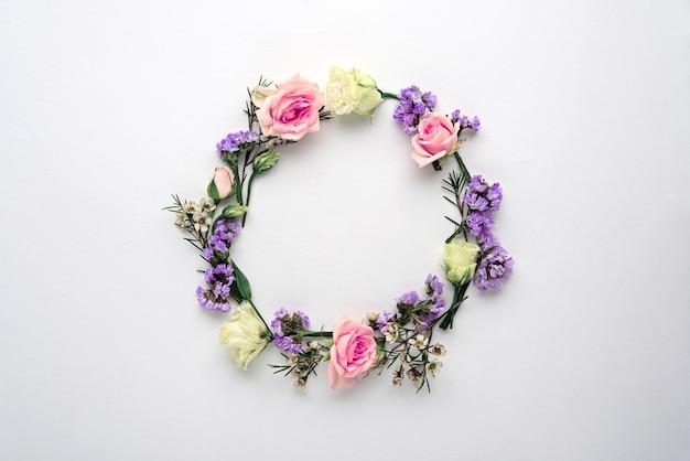花の輪、白い背景のフレーム、ピンクのバラの組成、リモニウム、コピースペースのあるトルコギキョウ、フラットレイ、上面図